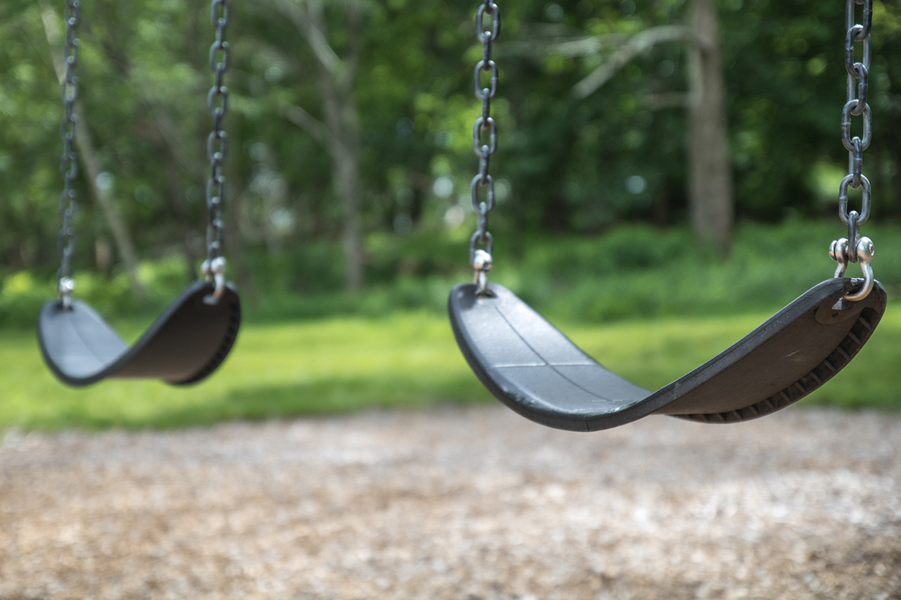 An empty pair of swings hang at the playground